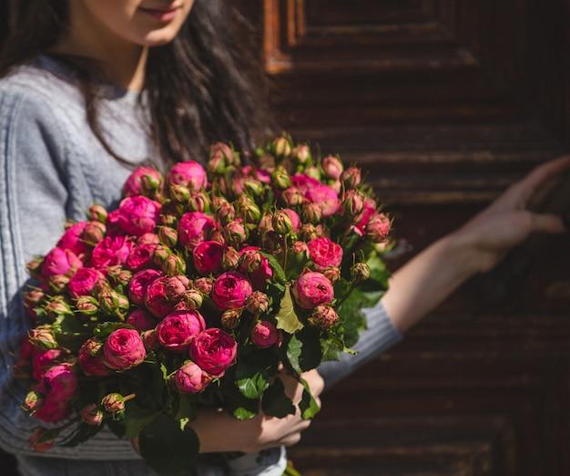 Een vrouw die een boeket van roze pioenrozen in de hand houdt