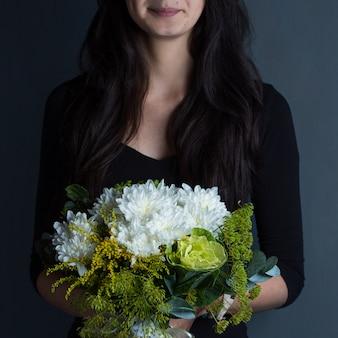 Een vrouw die een boeket van sneeuwwitte bloemen houdt dient de schietruimte in
