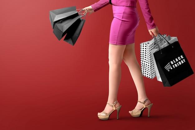 Een vrouw die een boodschappentas met black friday-tekst over een rood draagt