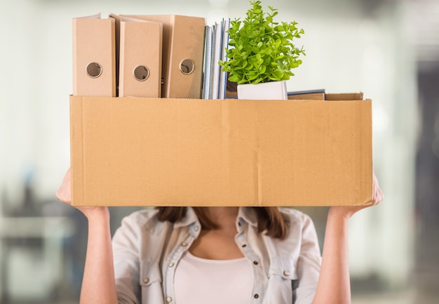 Een vrouw die een doos in een bureau steunt.