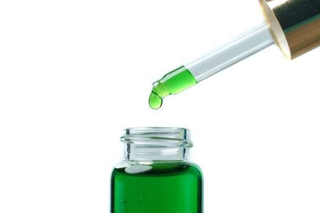 Een vrouw die een druppelaar met groene hennepolie vloeistof houdt. laboratorium concept.