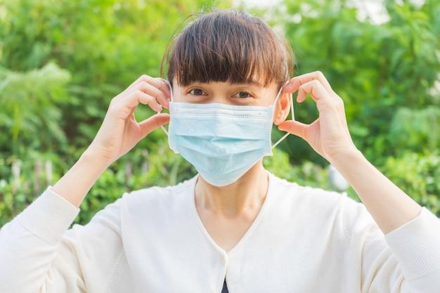 Een vrouw die een gezichtsmasker draagt met een blij gezicht om stof de verspreiding van ziektekiemen en bacteriën te voorkomen en infecties corona-virus te voorkomen. hygiëne concept