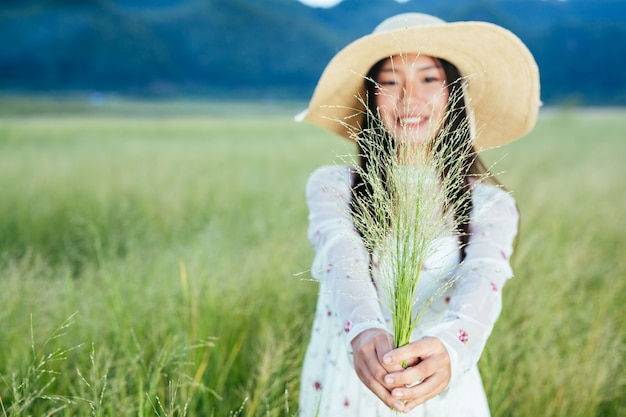 Een vrouw die een gras in haar handen houdt op een prachtig grasveld met een berg.