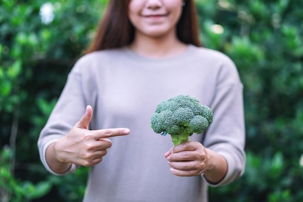 Een vrouw die een groene broccoli vasthoudt en wijst