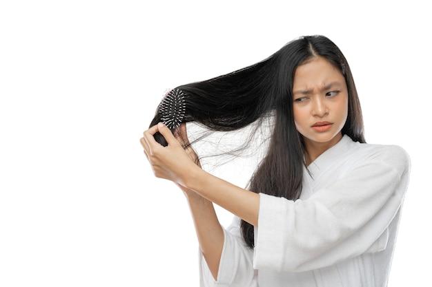 Een vrouw die een handdoek draagt en een kam gebruikt met een uitdrukking van frustratie