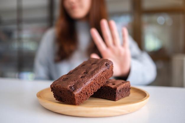 Een vrouw die een handteken maakt om een browniecake in een houten bord te weigeren