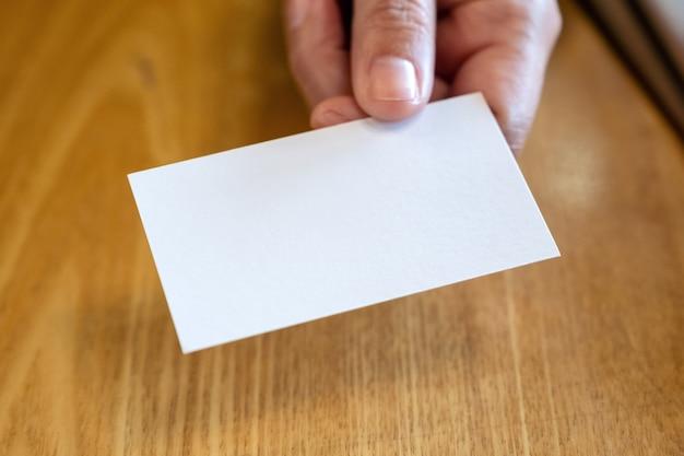 Een vrouw die een leeg leeg visitekaartje vasthoudt en aan iemand geeft