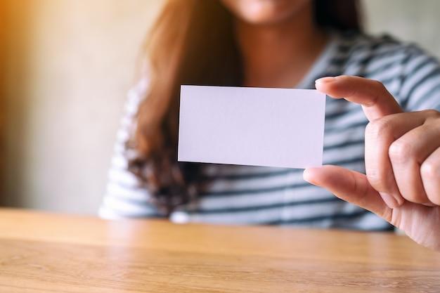 Een vrouw die een leeg, leeg visitekaartje vasthoudt en toont