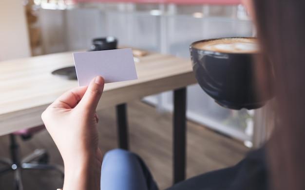 Een vrouw die een leeg visitekaartje houdt terwijl het drinken van koffiekop