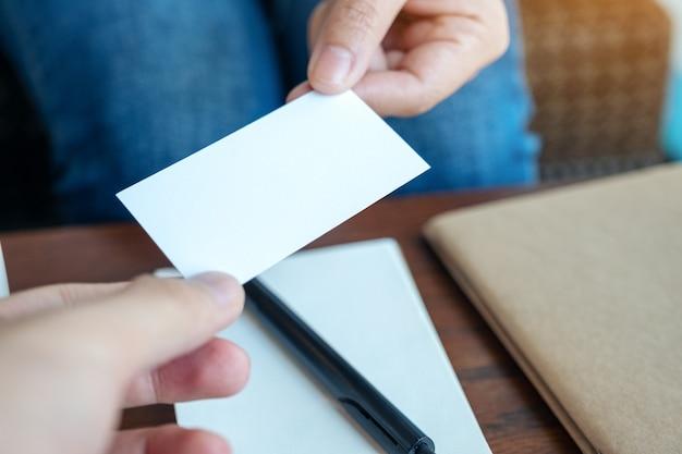 Een vrouw die een leeg visitekaartje vasthoudt en aan iemand geeft