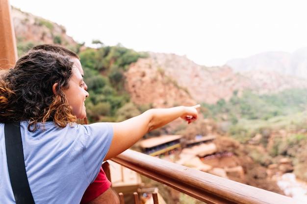 Een vrouw die een man omhelst die naar de horizon wijst voor een dor landschap met kleine huisjes. ouzoud-watervallen in marokko