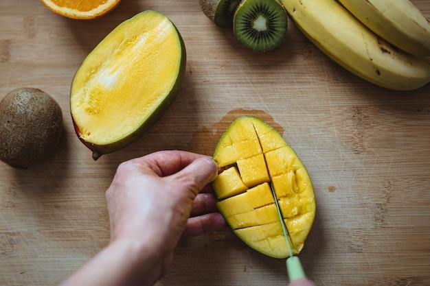 Een vrouw die een mango snijdt met een groen mes op een houten tafel omringd door ander fruit (bovenaanzicht).