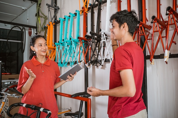 Een vrouw die een pad vasthoudt, praat met een mannelijke winkelbediende terwijl ze een fietsframe regelt