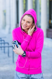Een vrouw die een roze jasje draagt dat haar hoofdtelefoons zet
