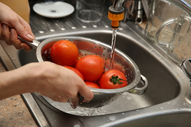 Een vrouw die een vergiet en een gootsteen gebruikt om tomaten te wassen.