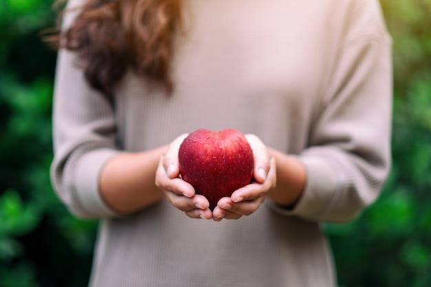 Een vrouw die een verse rode appel in handen houdt