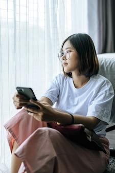 Een vrouw die een wit overhemd draagt, op het bed zit en een smartphone speelt.