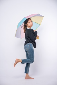 Een vrouw die een zwart overhemd draagt en met een paraplu staat