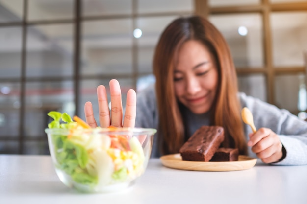Een vrouw die ervoor kiest browniecake te eten en een handteken maakt om een groentesalade op tafel te weigeren