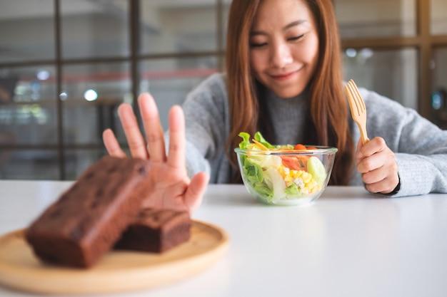 Een vrouw die ervoor kiest om groentesalade te eten en een handteken maakt om een browniecake op tafel te weigeren