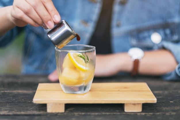 Een vrouw die espresso giet schoot in een glas ijs en citroen