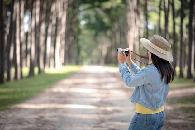 Een vrouw die foto met digitale camera in pijnboombos neemt