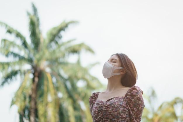 Een vrouw die gezichtsmasker in het park draagt. corona-virus of covid-19-beschermingsconcept.