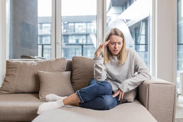 Een vrouw die haar hoofd vasthoudt bezorgd over een ondraaglijke hoofdpijn