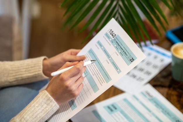 Een vrouw die het papier vasthoudt om belastingkosten te tellen