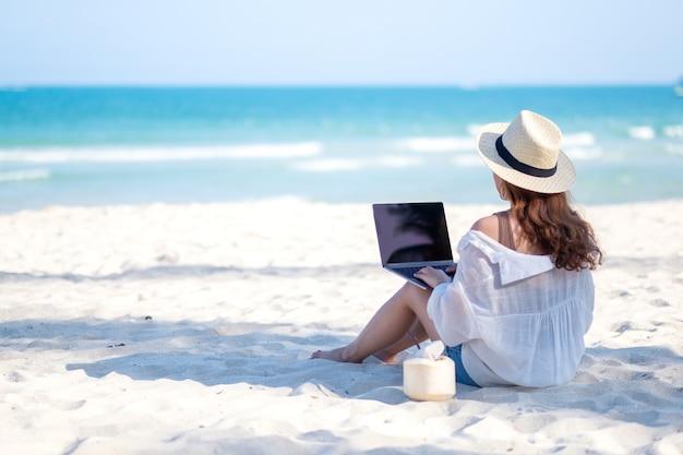 Een vrouw die het toetsenbord van een laptop gebruikt en typt terwijl ze op een prachtig strand zit