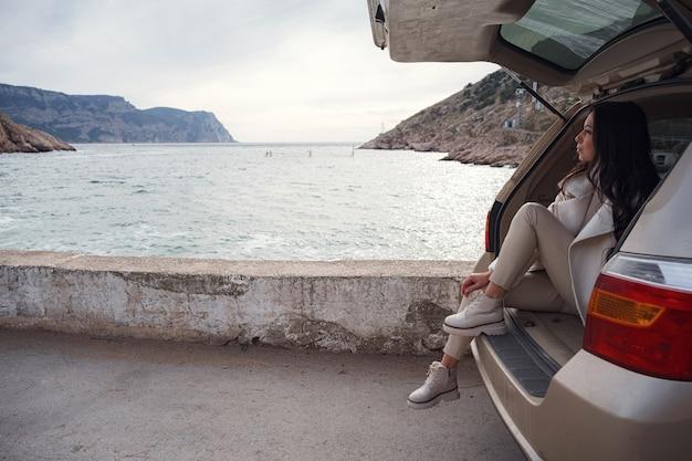 Een vrouw die in de kofferbak van een auto rust en uitkijkt over de zee. herfstrit bij zonsondergang. het concept van bewegingsvrijheid. herfstweekend. alleen reizen of solo reisconcept.
