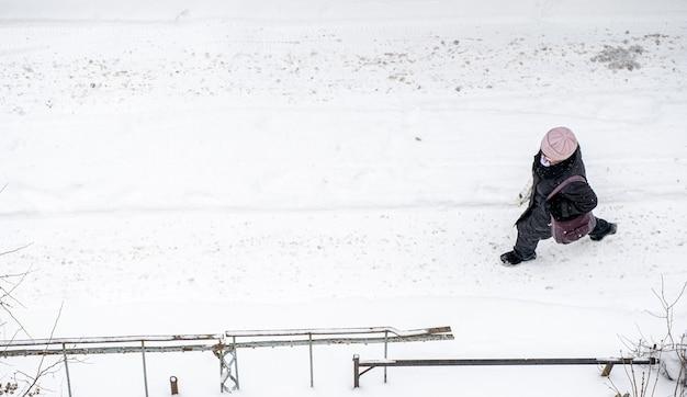 Een vrouw die in de winter in de sneeuw loopt
