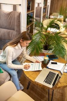 Een vrouw die in een gezellige sfeer werkt met papieren en laptop