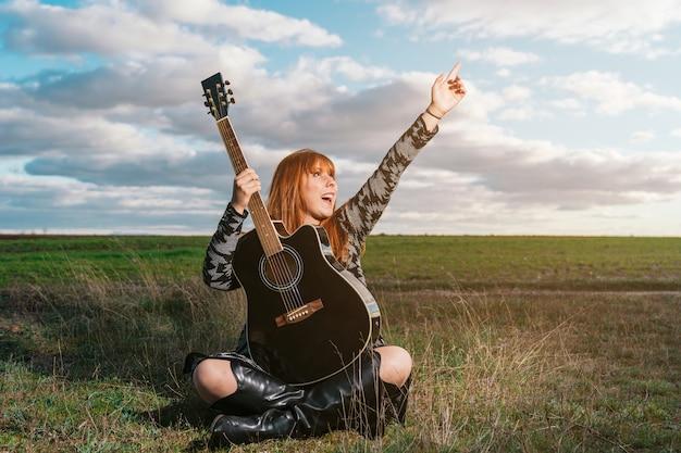 Een vrouw die in een park zit en een zwarte gitaar vasthoudt, opgewonden over het schouwspel