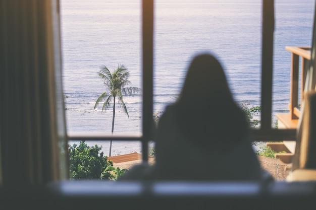 Een vrouw die in het bed zit en door het raam naar het prachtige uitzicht op zee kijkt nadat ze 's ochtends wakker wordt