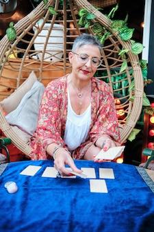 Een vrouw die kaarten deelt om de toekomst te vertellen met behulp van tarot - esoterisch concept