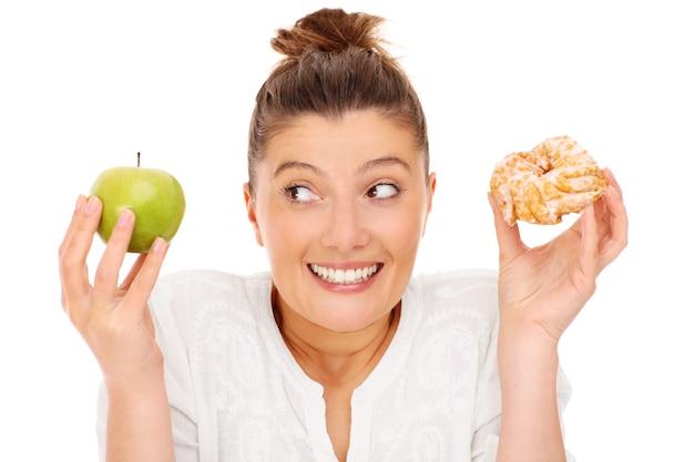 Een vrouw die kiest tussen appel en donut