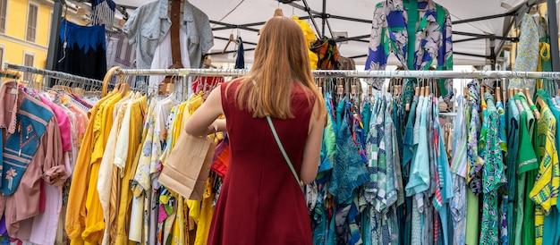 Een vrouw die kleren bekijkt op de markt