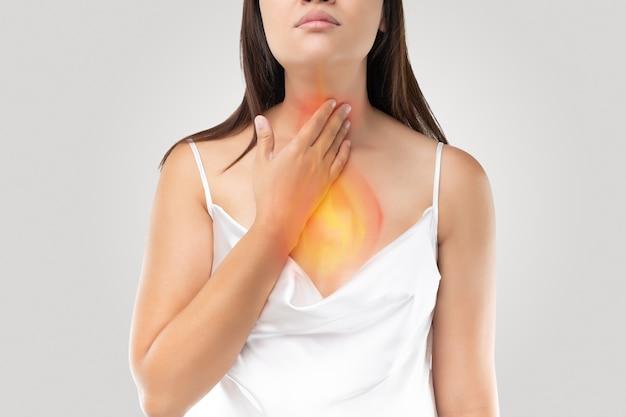 Een vrouw die lijdt aan zure reflux of zuurbranden op grijs