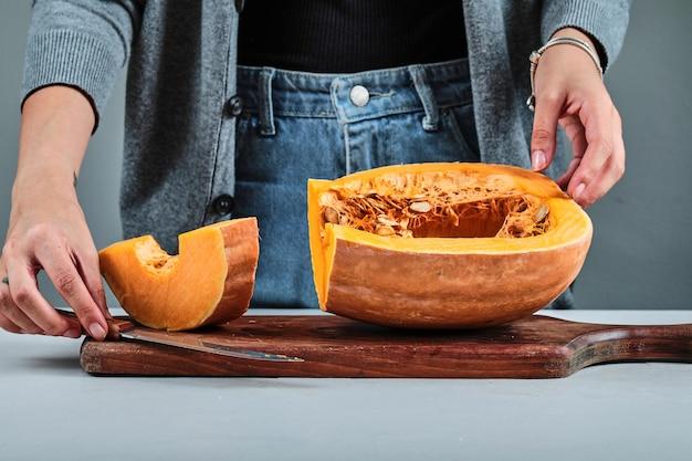 Een vrouw die met de hand een plakje pumpkon snijdt met mes op een houten bord.