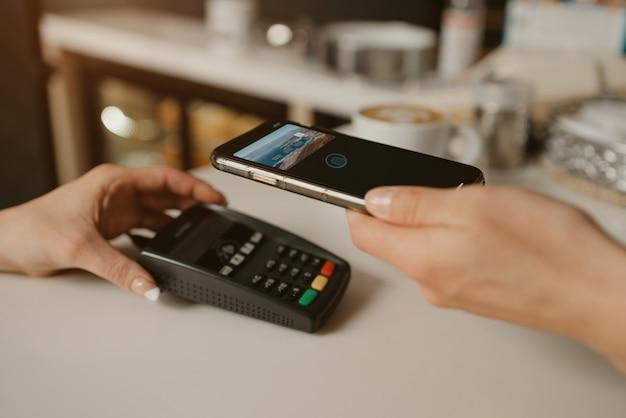 Een vrouw die met een smartphone betaalt door contactloze technologie in een café
