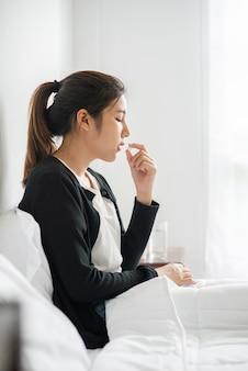 Een vrouw die niet lekker op de bank ligt en op het punt staat antibiotica te nemen.