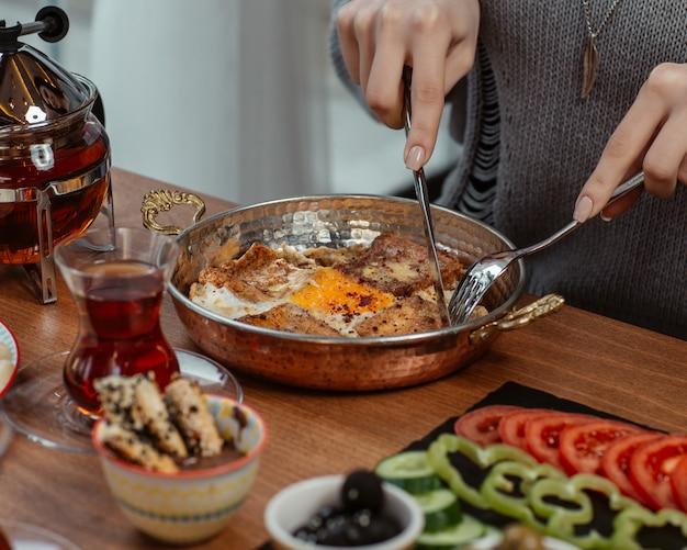 Een vrouw die ontbijtomelet eet in een pan, rond een tafel gedoneerd met olijven, groenten en zwarte thee.