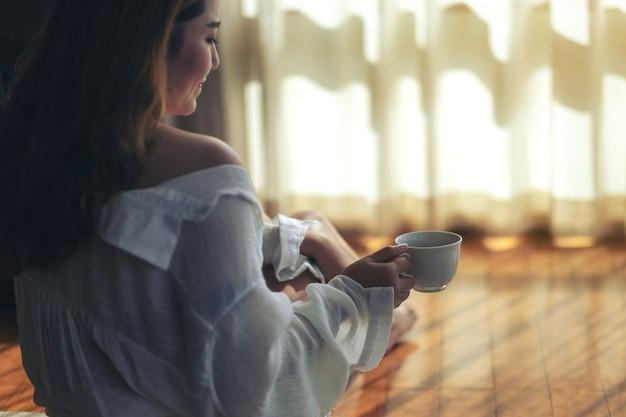 Een vrouw die op de grond zit en 's ochtends een kop warme koffie vasthoudt om te drinken