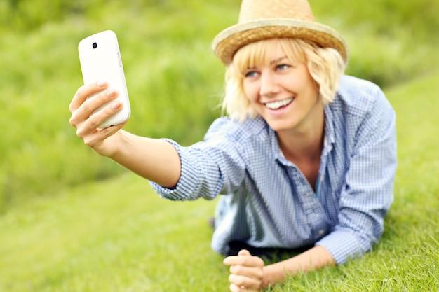 Een vrouw die op het gras ligt en foto's maakt met een mobiele telefoon
