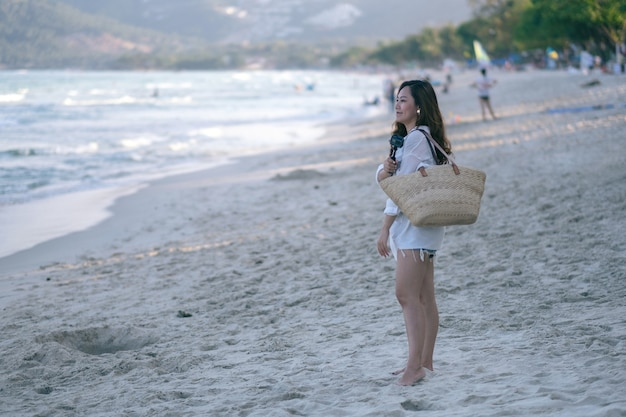 Een vrouw die over het strand slentert en naar een prachtig uitzicht op zee kijkt