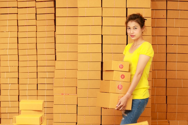 Een vrouw die pakjes draagt die klaar zijn om online te winkelen, werkt bij haar thuis.