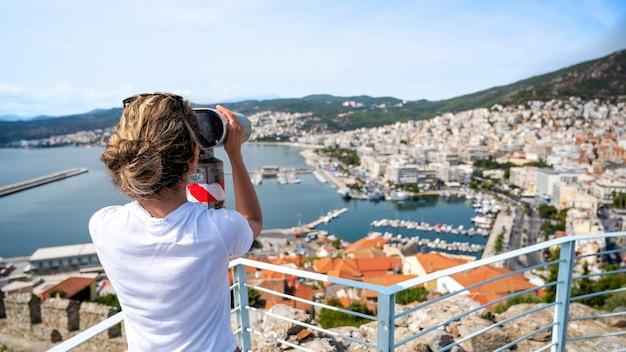 Een vrouw die stationaire verrekijker onderzoekt in kavala, griekenland