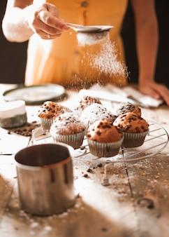 Een vrouw die suiker op eigengemaakte muffins op koelrek bestrooit