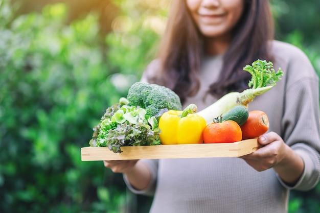 Een vrouw die verse gemengde groenten in een houten dienblad houdt